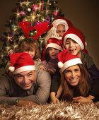 Closeup portrait of big happy family with Santa Claus lying down near Christmas tree, holiday celebr
