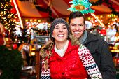 image of merry-go-round  - Man and woman or  a couple  or friends during advent season or holiday in front of a carousel or merry - JPG