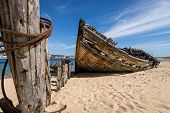 stock photo of shipwreck  - An old shipwreck on a sunny beach - JPG