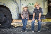 stock photo of denim wear  - Two Young Boys Wearing Cowboy Hats Leaning Against an Antique Truck in a Rustic Country Setting - JPG