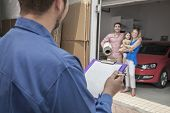 stock photo of movers  - Mover holding clipboard and invoice with family in the background - JPG