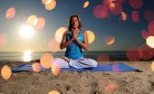 stock photo of padmasana  - full lotus yoga position and meditation on beach - JPG