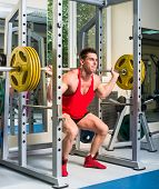 image of squatting  - weightlifter squats with a barbell - JPG