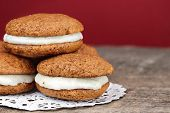 stock photo of whoopees  - Stack of homemade Pumpkin Whoopie Pies or Moon Pies made with cream cheese frosting - JPG