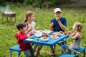 stock photo of brazier  - Four children eat meat with vegetables at the picnic on pembroke table - JPG