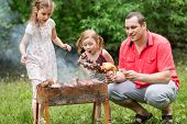 stock photo of bonfire  - A family of three making barbecue on the grill on nature - JPG
