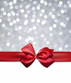 stock photo of ribbon decoration  - Christmas silver bokeh background with red bow - JPG