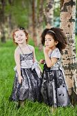 Two little girls in beautiful black gowns stand on grassy lawn near tree in park, focus on mulatto