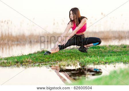Woman training near lake at sunset