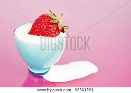 Strawberry In Blue Cup With Yoghurt Spill