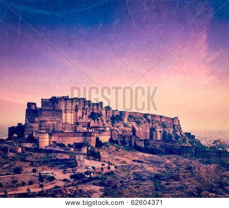 Vintage retro hipster style travel image of Mehrangarh Fort in twilight on sunset, Jodhpur, Rajasthan, India  with grunge texture overlaid