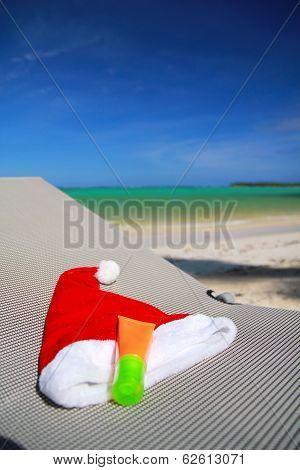Santa Hat And Sun Tan On Chaise Longue