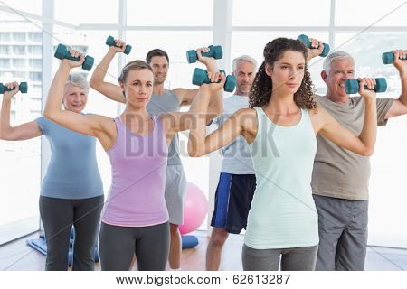 Fitness class exercising with dumbbells in a bright gym
