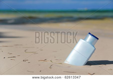 Blue Bottle With Sunblock Lotion In Sand On Tropical Beach