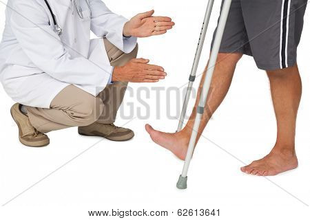 Low section of a doctor with senior man using walker over white background