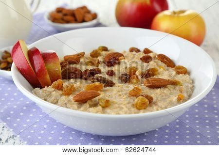 Tasty oatmeal with raisins and apples on wooden table