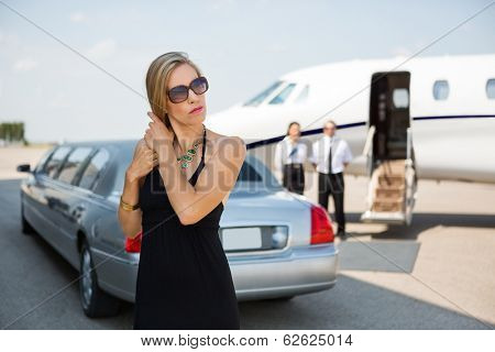 Elegant woman standing against limousine and private jet at airport terminal