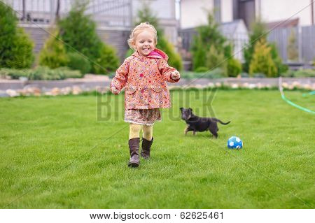Cute little girl playing with her puppy in the yard