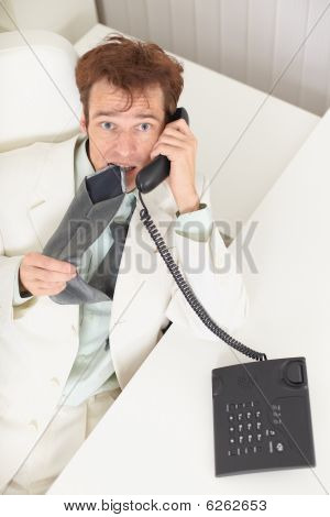 Young Businessman Speaks On Phone, Worries And Bites Tie