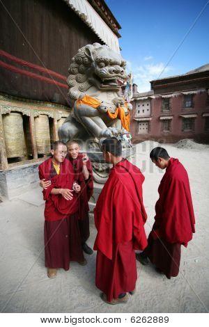 Four tibetan lama students before a monastery