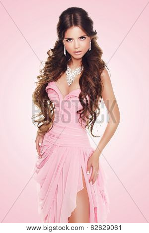 Beautiful Brunette Woman Wearing In Sexy Luxury Dress Over Pink Background. Fashion Beauty Model Gir