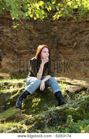 Girl sitting at stone in forst