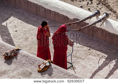 THIKSEY, INDIA - SEPTEMBER 4, 2011: Two Tibetan Buddhist monks blowing Tibetan horn (dungche) during morning pooja, Thiksey gompa, Ladakh, India