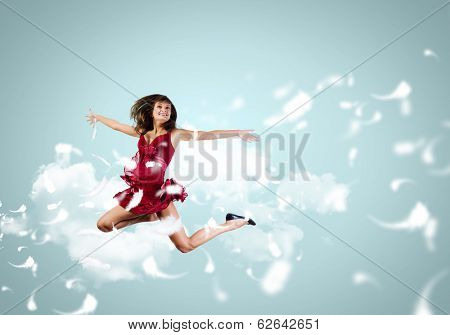 Young attractive woman in red dress jumping high