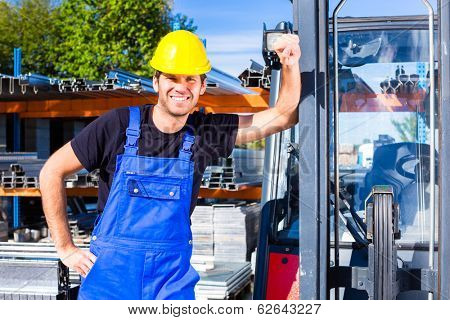 builder or driver with pallet transporter or lift fork truck on construction or building site