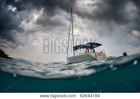 Split shot of anchored sail boat with heavy clouds in sky