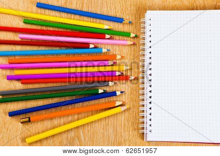 Colored pencils and notepad on wooden table