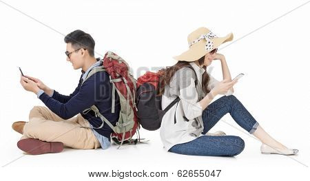 Asian young couple traveling and sitting on ground back to back and using mobile phone, full length portrait on white background.