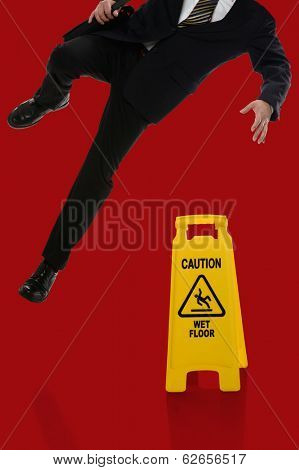 Businessman slipping on wet floor in front of caution sign over red background