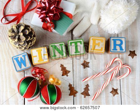 Childrens blocks spelling out Winter on rustic wooden boards The word is surrounded by candy canes, ornaments, pine cone, ribbon, bows and presents and other seasonal items. Horizontal format.