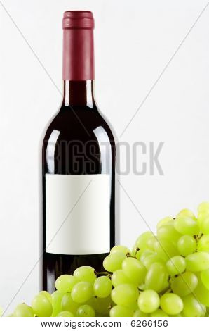 Bottle Of Red Wine And Green Grapes In Front