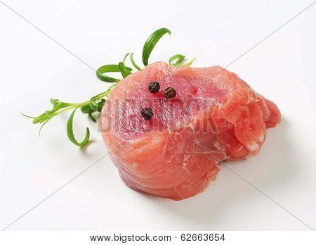 raw pork tenderloin medallion with black pepper and thyme