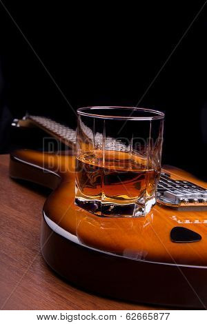 glass of rum and plectrum on the electric guitar