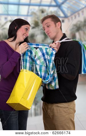 Young Woman Showing Her Friend A Shirt While Shopping In A Mall