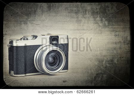 Vintage rangefinder style camera on a grunge background simulating an old film frame with space for text