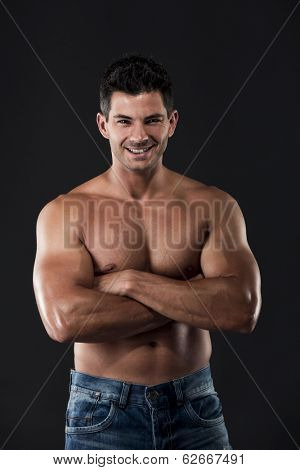Portrait of a muscular man posing without a shirt against dark background