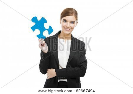 Beautiful young business woman holding a blue puzzle piece, over a white background