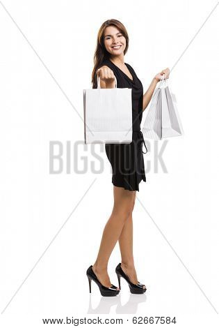 Beautiful and attractive young woman with arms up holding shopping bags, isolated over white background