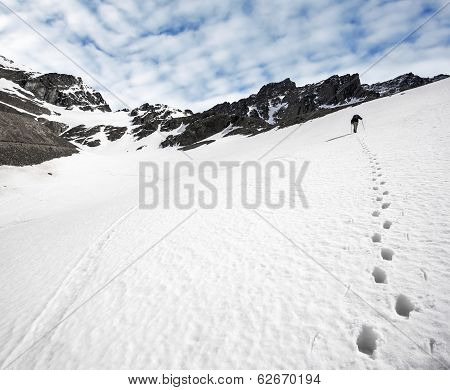 Trekker And Footprints In The Snow.