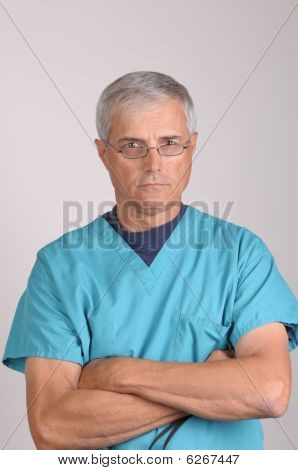 Middle Aged Doctor In Scrubs With Arms Crossed