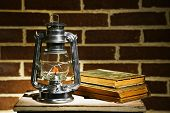 image of kerosene lamp  - Burning kerosene lamp and books on brick wall background - JPG