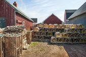 Stacks of wooden lobster traps between rustic buildings in North Rustico, Prince Edward Island, Cana
