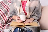 Woman sitting on sofa,  reading book and  drink coffee or tea, close-up
