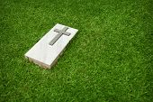 Marble Tombstone With The Christian Cross On A Green Lawn