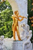 Gorgeous gilded statue of Johann Strauss with violin in Vienna park