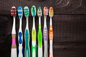 picture of toothbrush  - Colorful toothbrushes on black wooden background - JPG